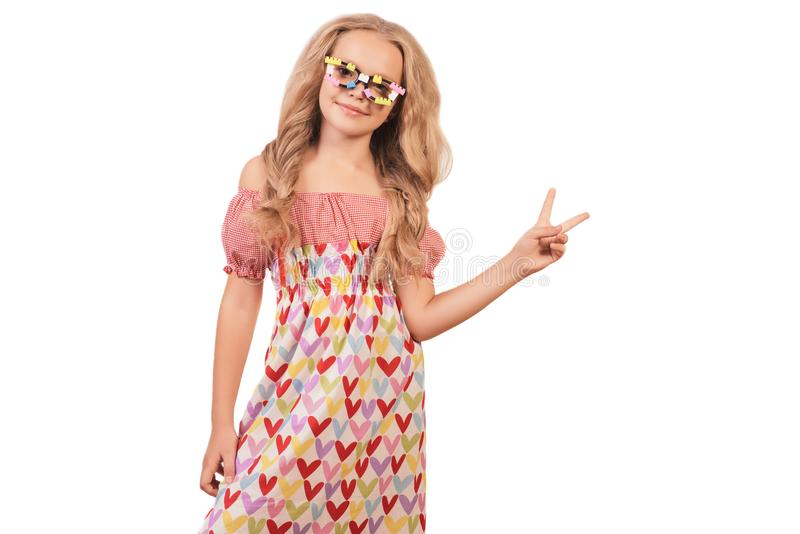 Gelukkig meisje in glazen en kleding met harten die vredesteken tonen stock afbeelding