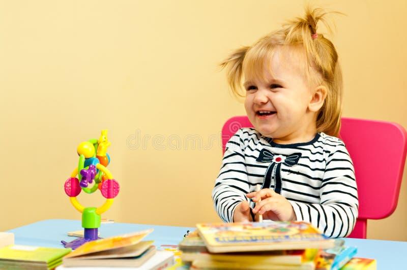 Gelukkig meisje met boeken en stuk speelgoed stock afbeeldingen