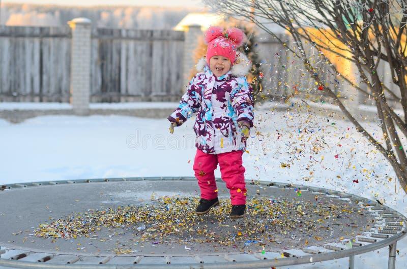 Gelukkig meisje met confettien op de trampoline stock afbeelding