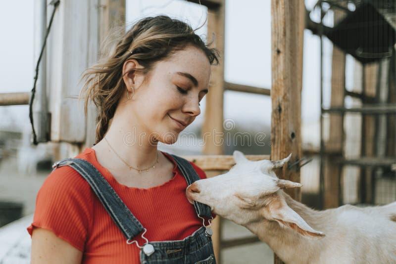 Gelukkig meisje met een leuke geit stock fotografie