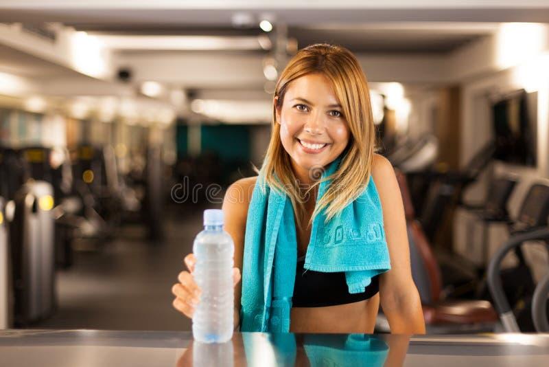 Gelukkig meisje met fles van water en handdoek in een geschiktheidsclub royalty-vrije stock foto's