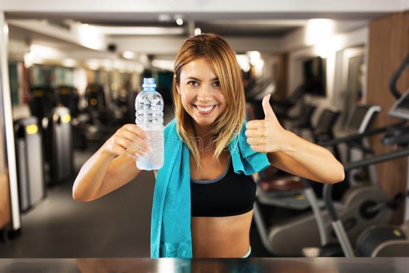 Gelukkig meisje met fles van water en handdoek in een geschiktheidsclub stock afbeelding
