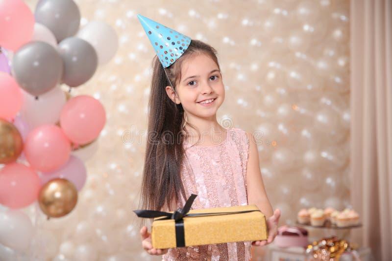 Gelukkig meisje met gift in prachtig verfraaide ruimte stock foto's