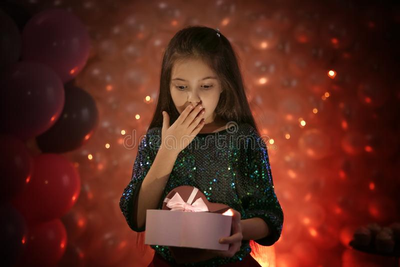 Gelukkig meisje met gift in prachtig verfraaide ruimte stock afbeelding