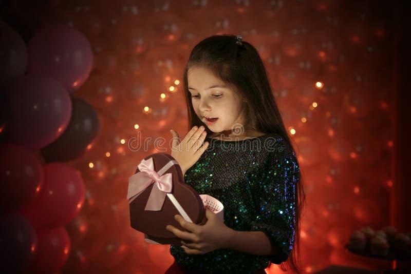 Gelukkig meisje met gift in prachtig verfraaide ruimte stock fotografie