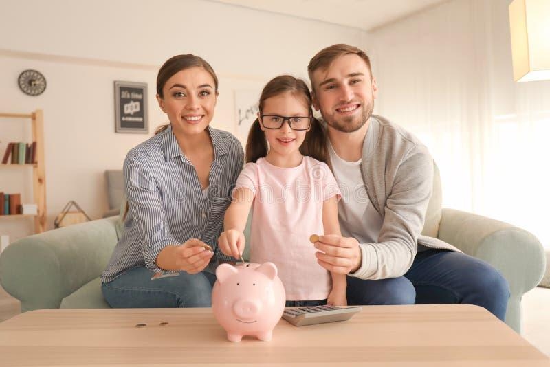 Gelukkig meisje met haar ouders die piggy muntstukken binnen zetten in bank De besparingenconcept van het geld stock foto's