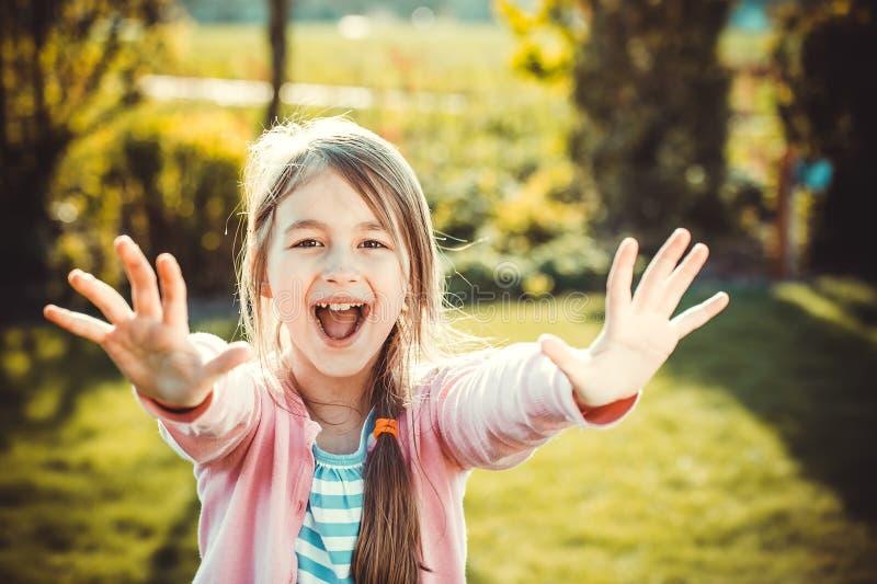 Gelukkig meisje met handen omhoog in de zomerpark royalty-vrije stock foto's