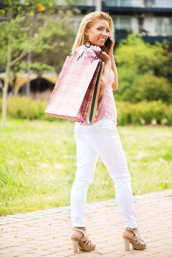 Gelukkig meisje met het winkelen zakken die een telefoongesprek hebben stock afbeeldingen