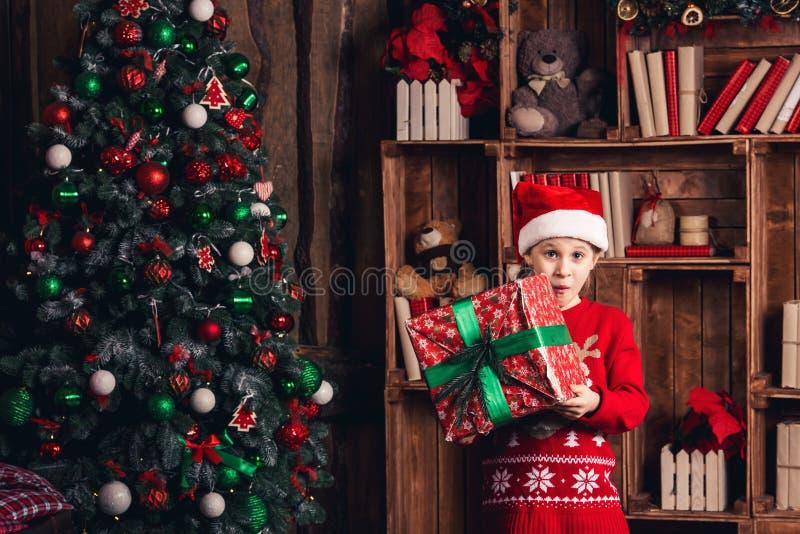Gelukkig meisje met Kerstmis van de verrassingsholding huidig in haar handen royalty-vrije stock afbeeldingen