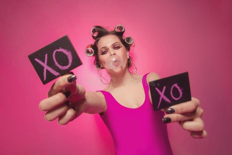 Gelukkig meisje met kleine raad en tekst XO op het in handen die op roze achtergrond in lichaam, met krulspelden op hoofd stellen stock fotografie
