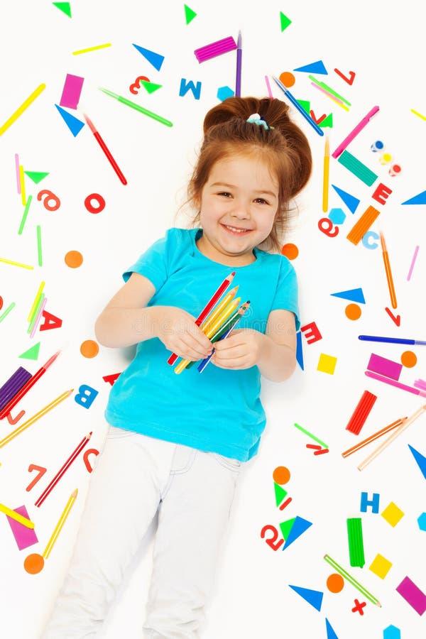 Gelukkig meisje met kleurpotloden bij haar hand stock fotografie