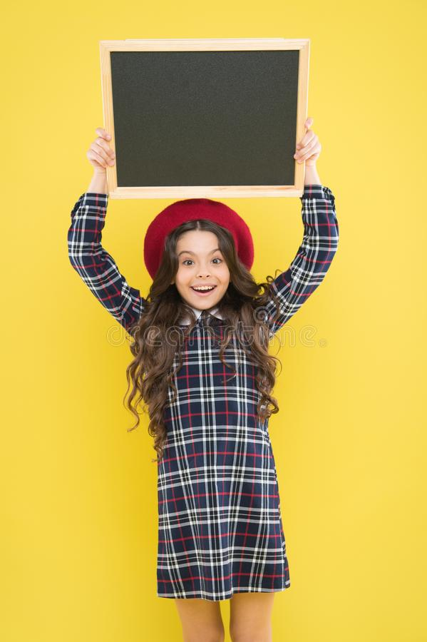 Gelukkig meisje met lang krullend haar in baret kind met leeg bord Parijse kind op geel De ruimte van het exemplaar bevordering royalty-vrije stock afbeeldingen