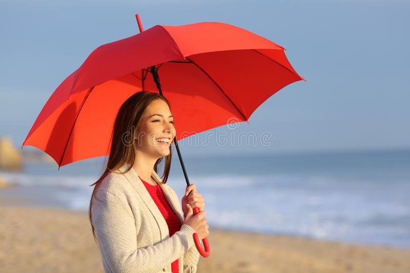 Gelukkig meisje met rode paraplu het letten op zonsondergang op het strand royalty-vrije stock foto