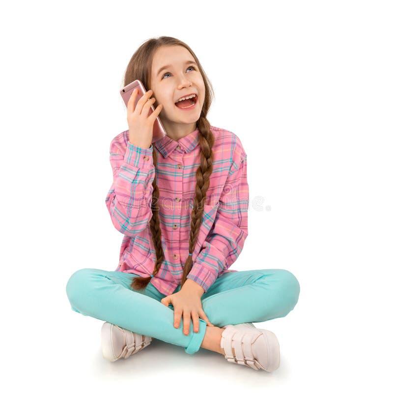 Gelukkig meisje met slimme die telefoonzitting op vloer op witte achtergrond wordt geïsoleerd Mensen, kinderen, technologie royalty-vrije stock foto