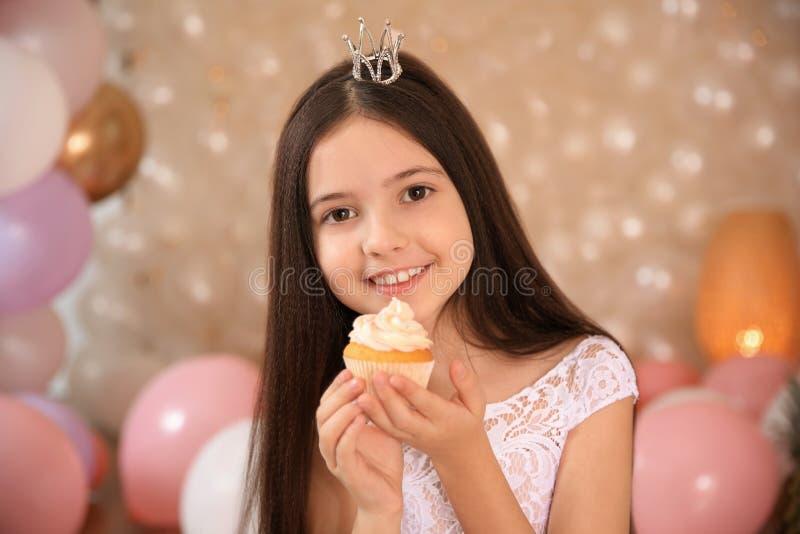 Gelukkig meisje met verjaardag cupcake in prachtig verfraaide ruimte stock foto's