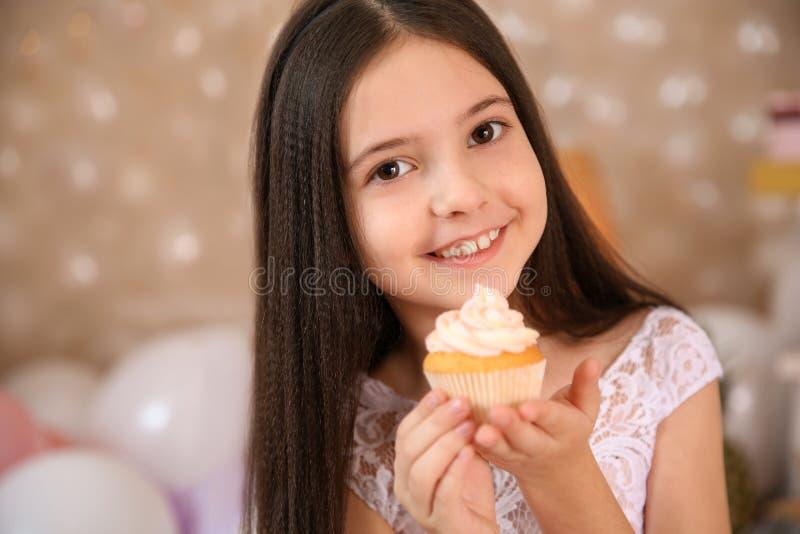 Gelukkig meisje met verjaardag cupcake in prachtig verfraaide ruimte royalty-vrije stock afbeelding