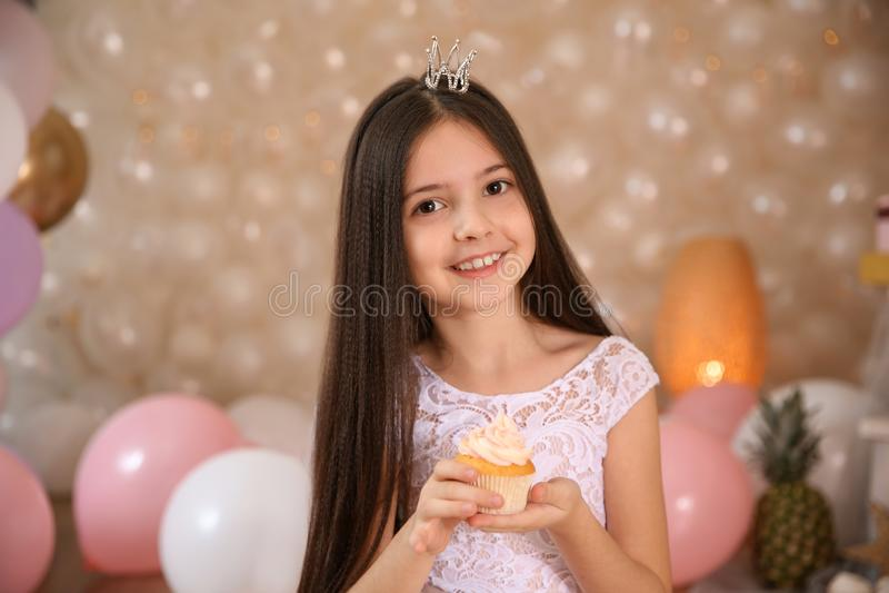Gelukkig meisje met verjaardag cupcake in prachtig verfraaide ruimte stock foto