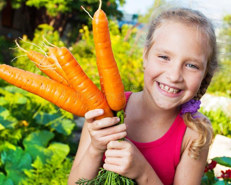 Gelukkig meisje met wortel stock afbeelding