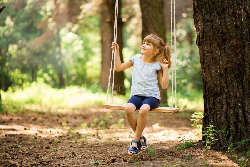 Gelukkig meisje op een schommeling in het park stock afbeeldingen