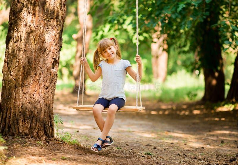 Gelukkig meisje op een schommeling in het park stock fotografie