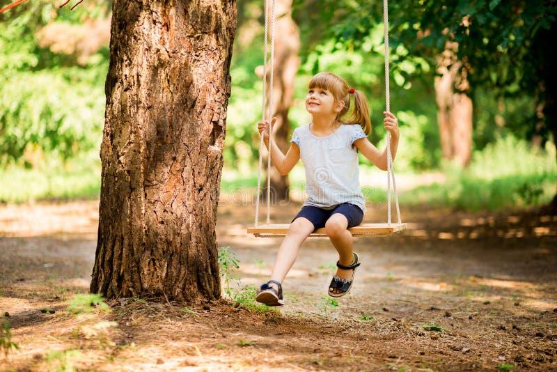 Gelukkig meisje op een schommeling in het park royalty-vrije stock fotografie