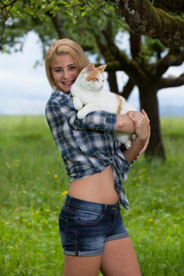 Gelukkig meisje op een weide die van de de zomerbloem een kat houden stock afbeeldingen
