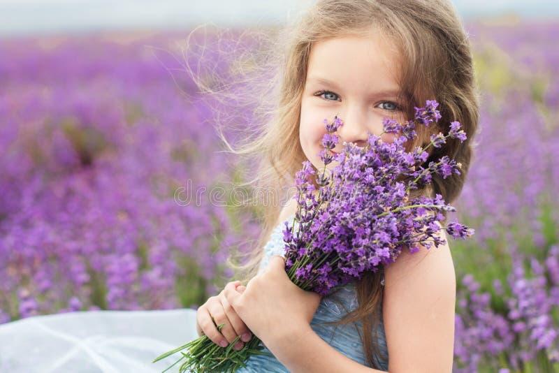Gelukkig meisje op lavendelgebied met boeket stock fotografie