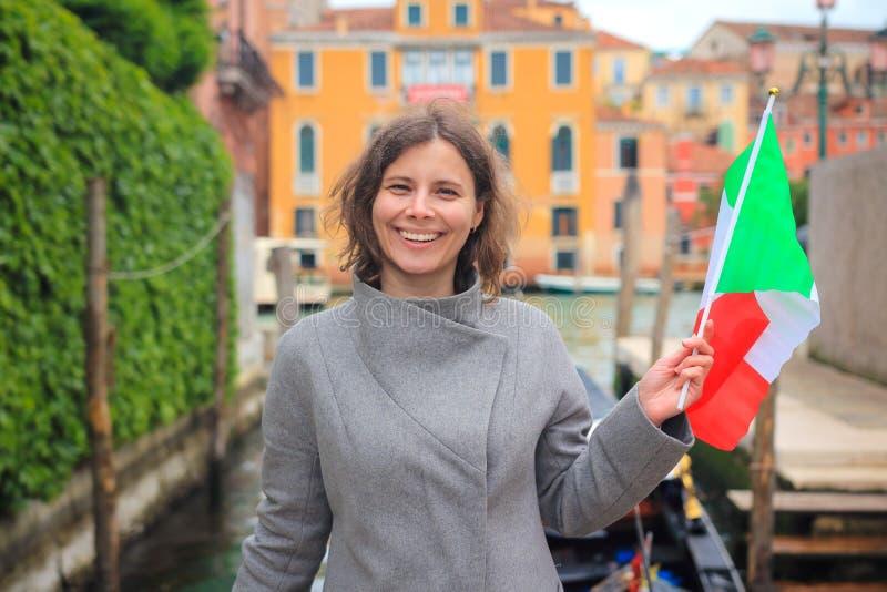 Gelukkig meisje op vakantie in Venetië Vrouw het stellen voor foto met Italiaanse vlag in Venezia, Italië Meisje op Venetiaans ka stock afbeeldingen