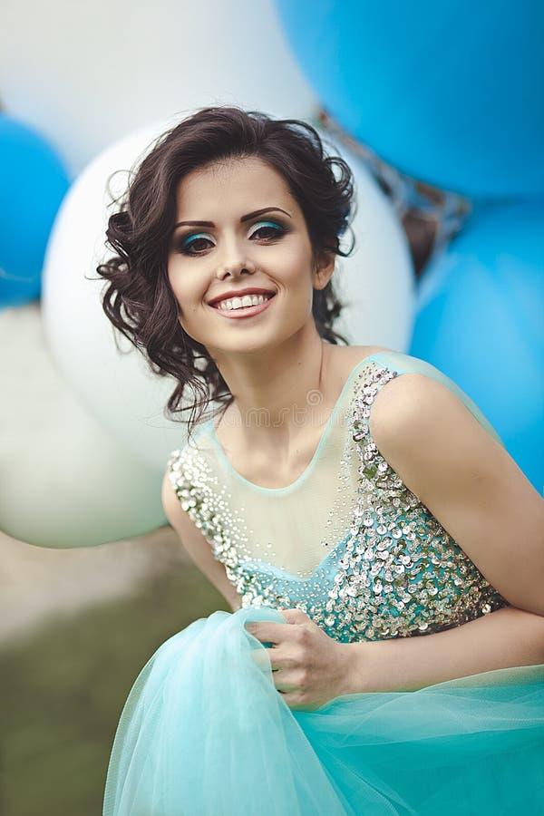 Gelukkig meisje in prom met de ballons van de heliumlucht Portret van een mooie meisjesgediplomeerde in een blauwe kleding stock afbeeldingen