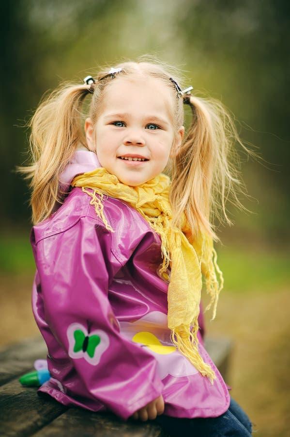 Gelukkig meisje in regenjas bij het park stock fotografie