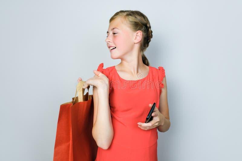 Gelukkig meisje in rode kleding die zich over grijze achtergrond bevinden Het winkelen concept royalty-vrije stock fotografie