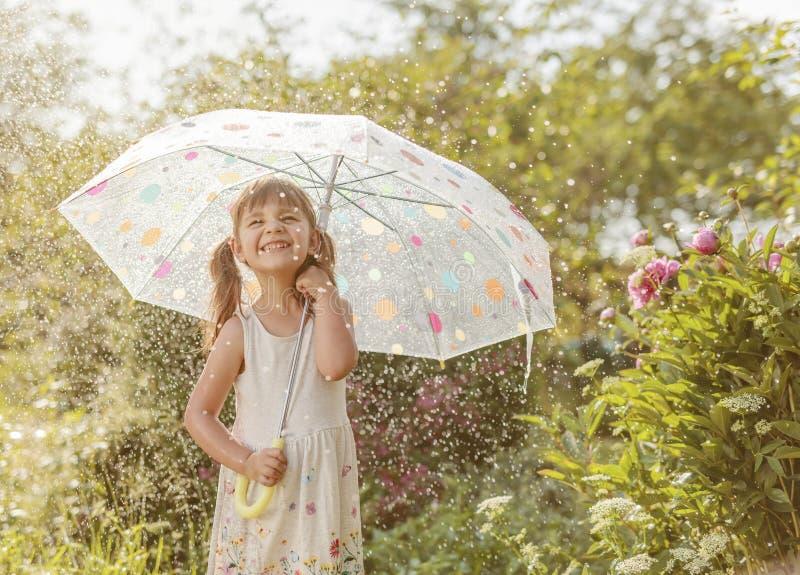 Gelukkig meisje in tuin onder de de zomerregen met een paraplu royalty-vrije stock afbeeldingen