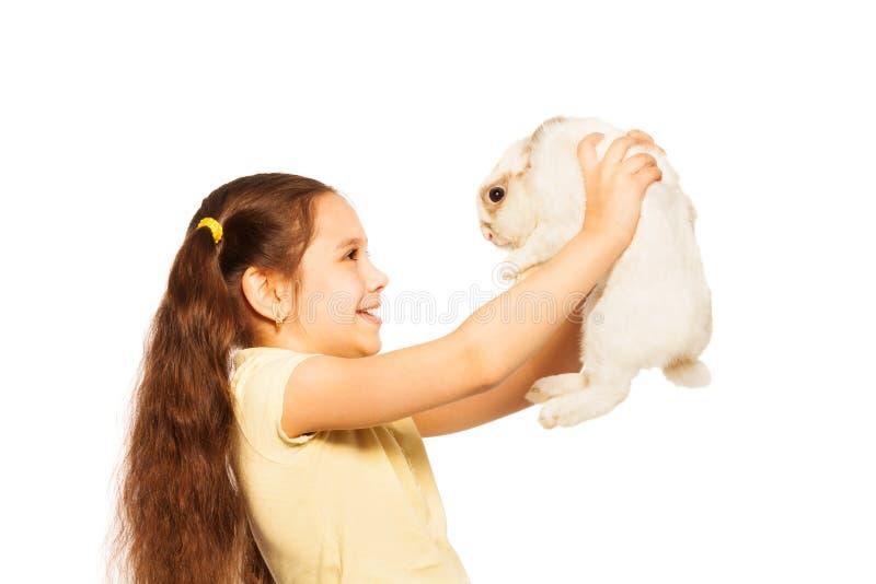Gelukkig meisjespel met klein wit konijn stock fotografie