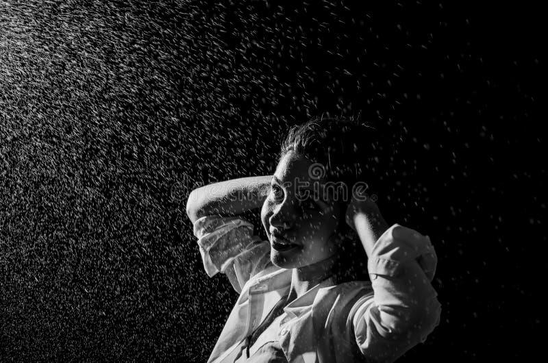 Gelukkig meisjesportret en bespattend water in haar gezicht mooi vrouwelijk model op zwarte achtergrond stock fotografie