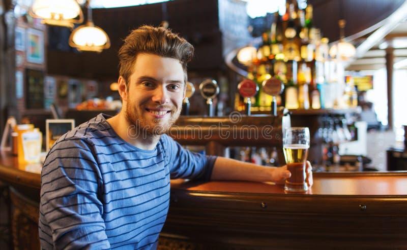 Gelukkig mens het drinken bier bij bar of bar stock foto