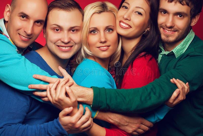 Gelukkig mensenconcept Portret van vijf modieuze dichte, en vrienden die glimlachen stellen samen koesteren stock afbeelding