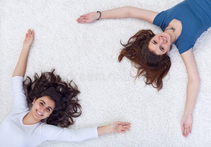 Gelukkig mensenframe - tieners die op de vloer leggen royalty-vrije stock foto
