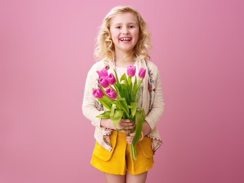 Gelukkig modern die meisje op roze met boeket van tulpen wordt geïsoleerd stock fotografie