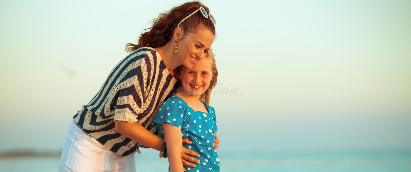 Gelukkig modern moeder en kind op strand bij zonsondergang het koesteren royalty-vrije stock foto's