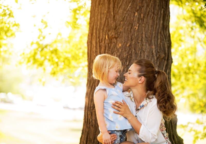 Gelukkig moeder en babymeisje die zich dichtbij boom bevinden stock foto's