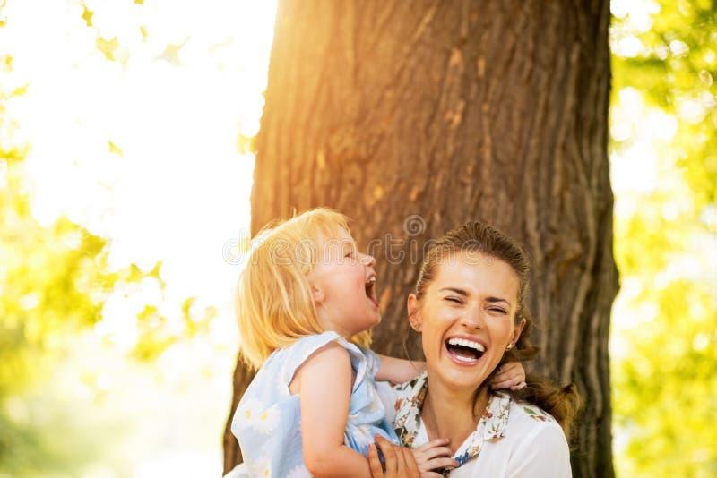 Gelukkig moeder en babymeisje die zich dichtbij boom bevinden royalty-vrije stock fotografie