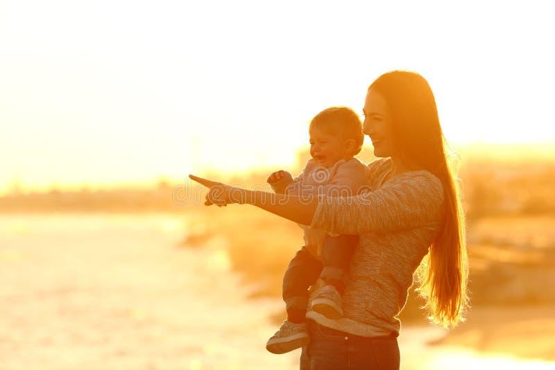 Gelukkig moeder en jong geitje die weg zonsondergang bekijken stock afbeeldingen