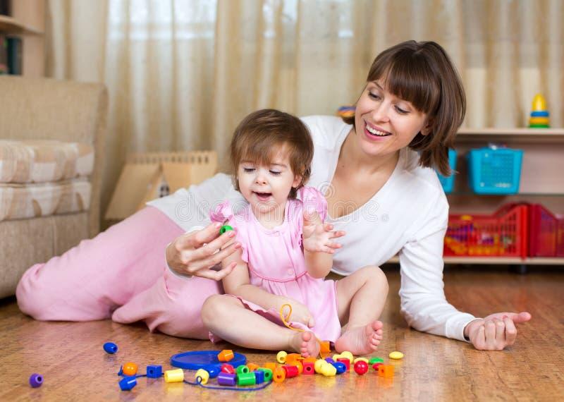 Gelukkig moeder en jong geitjespel thuis royalty-vrije stock foto's