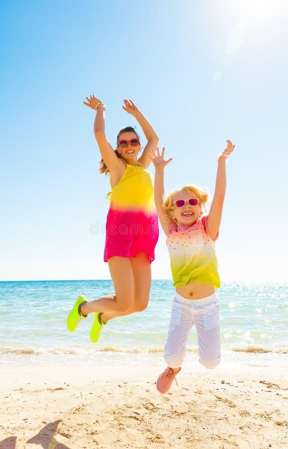 Gelukkig in moeder en kind bij zeekust het springen stock foto