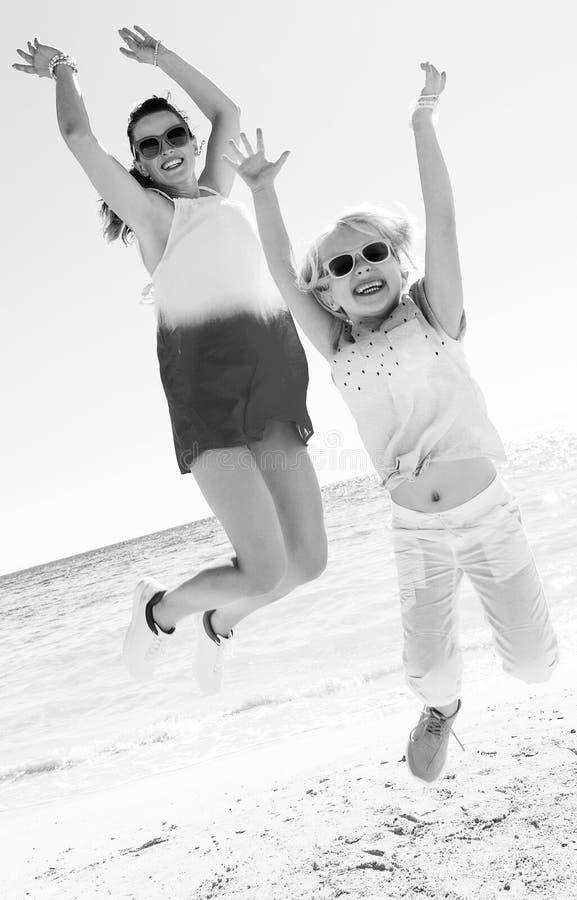 Gelukkig in moeder en kind bij zeekust het springen royalty-vrije stock fotografie