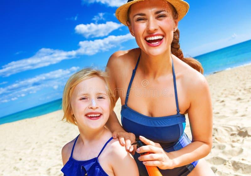 Gelukkig moeder en kind die op kust zonnebrandolie toepassen stock foto