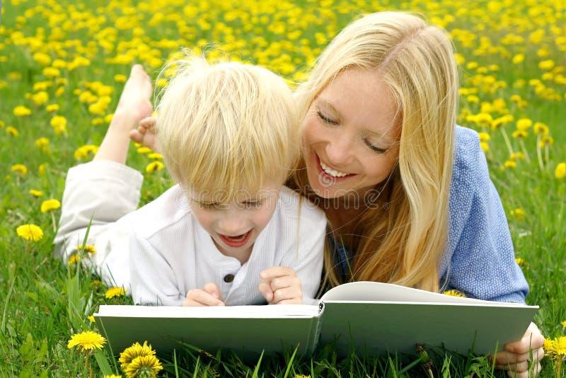 Gelukkig Moeder en Kindlezingsboek buiten in Weide stock afbeeldingen