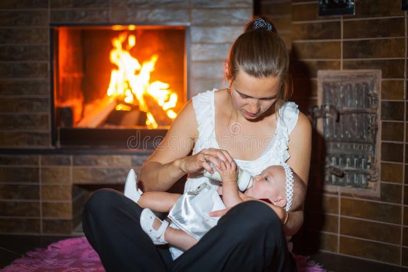 Gelukkig moeder met de fles gebracht groot babymeisje door de open haard royalty-vrije stock fotografie