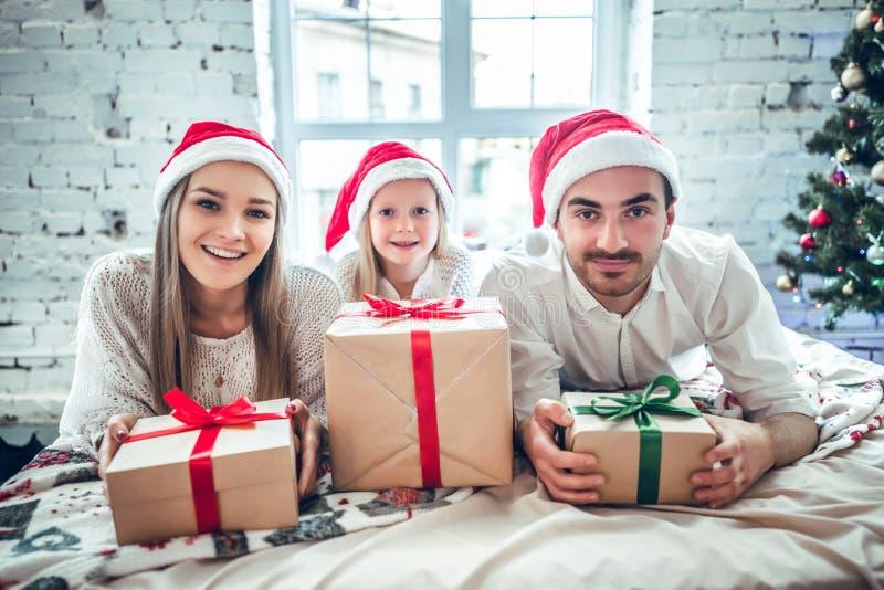 Gelukkig moeder, vader en meisje in de hoeden van de santahelper met giftdozen over woonkamer en de achtergrond van de Kerstmisbo stock afbeeldingen