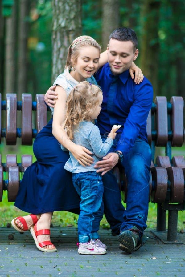 Gelukkig moeder, vader en meisje die in de zomerpark lopen royalty-vrije stock foto's